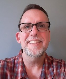 Hans Peterson staff photo. He has short brown hair and is wearing black glasses with a red flannel and smiling at the camera.