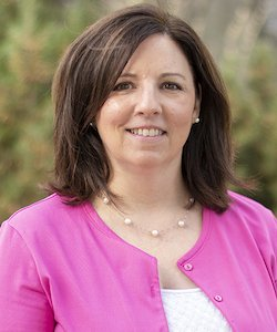 Laura Butler staff photo. She is wearing a white shirt with a pink sweater and pearl necklace. She has shoulder-length brown hair and is smiling at the camera
