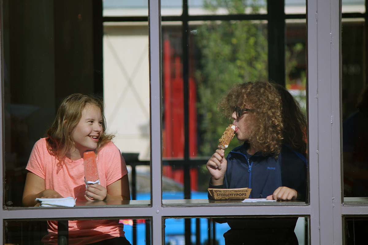 Photo of girl with Down syndrome and friend eating ice-cream.