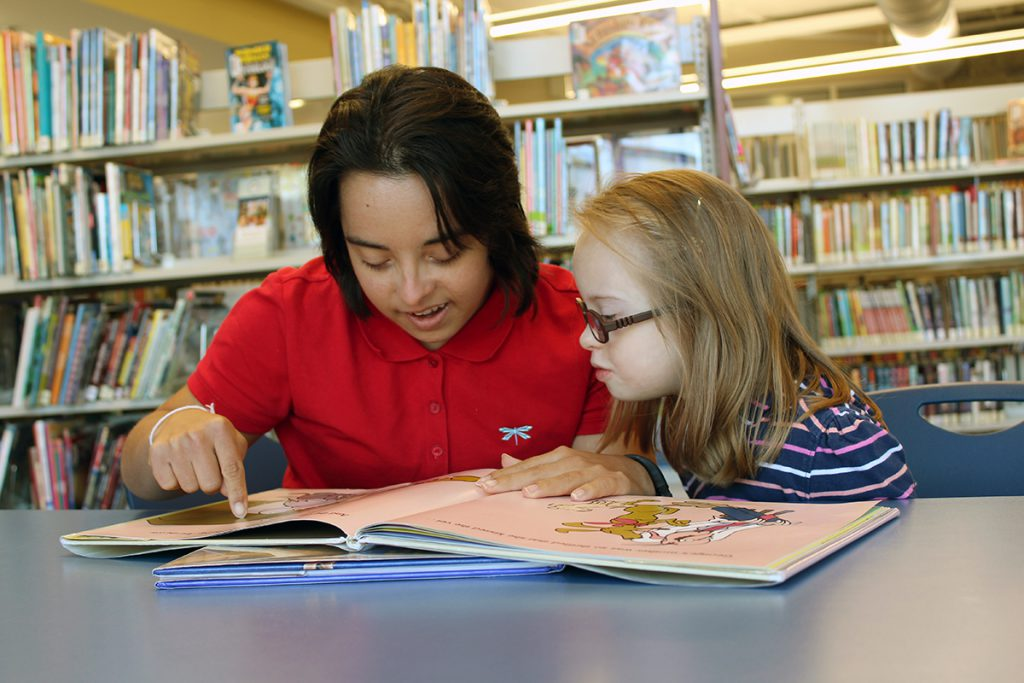 Photo of young woman with Down syndrome teaching reading to a child with Down syndrome.