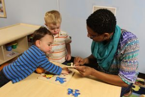 Two young preschool-aged boys working with a teacher on a puzzle.