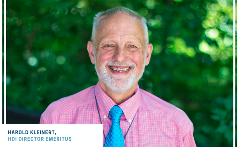 Harold Kleinert with white hair and beard smiling at the camera wearing a pink shirt and blue tie.