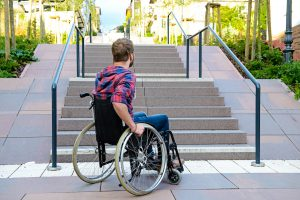 Man in a wheelchair looking up stair that are not accessible.