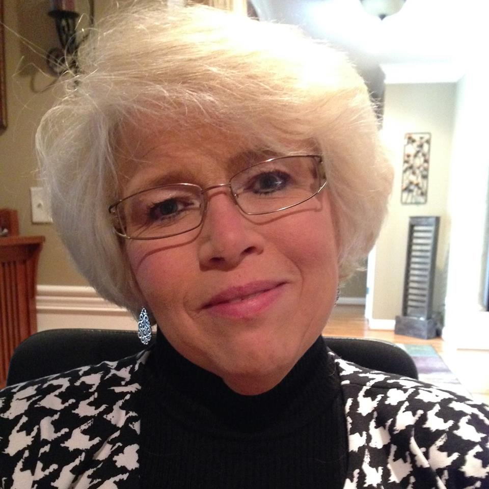 Photo of Marlene Huff, a white woman with white hair and glasses smiling and wearing black and white