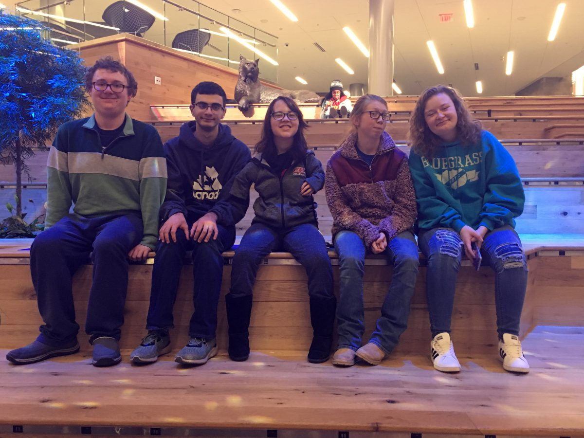 Five students with disabilities sitting on a bench, 2 boys and 3 girls