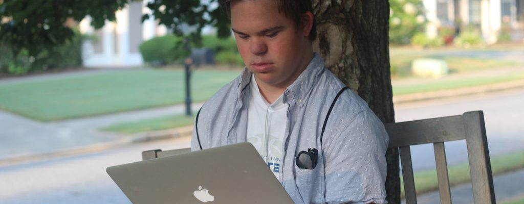 Young Man looking at laptop outdoors