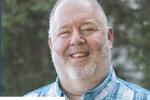 Man with gray beard smiling wearing blue shirt
