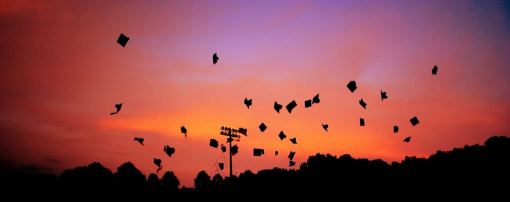 black graduation caps being thrown in the sunset sky