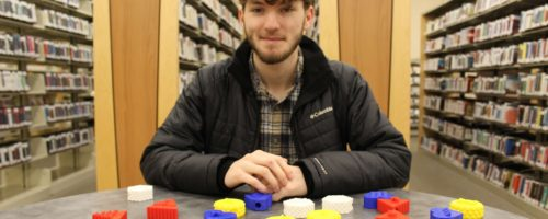 Young man with brown hair and beard wearing a black coat and brown flannel shirt seated at a library table in front of books. Multi-colored 3D printed objects are on the table.