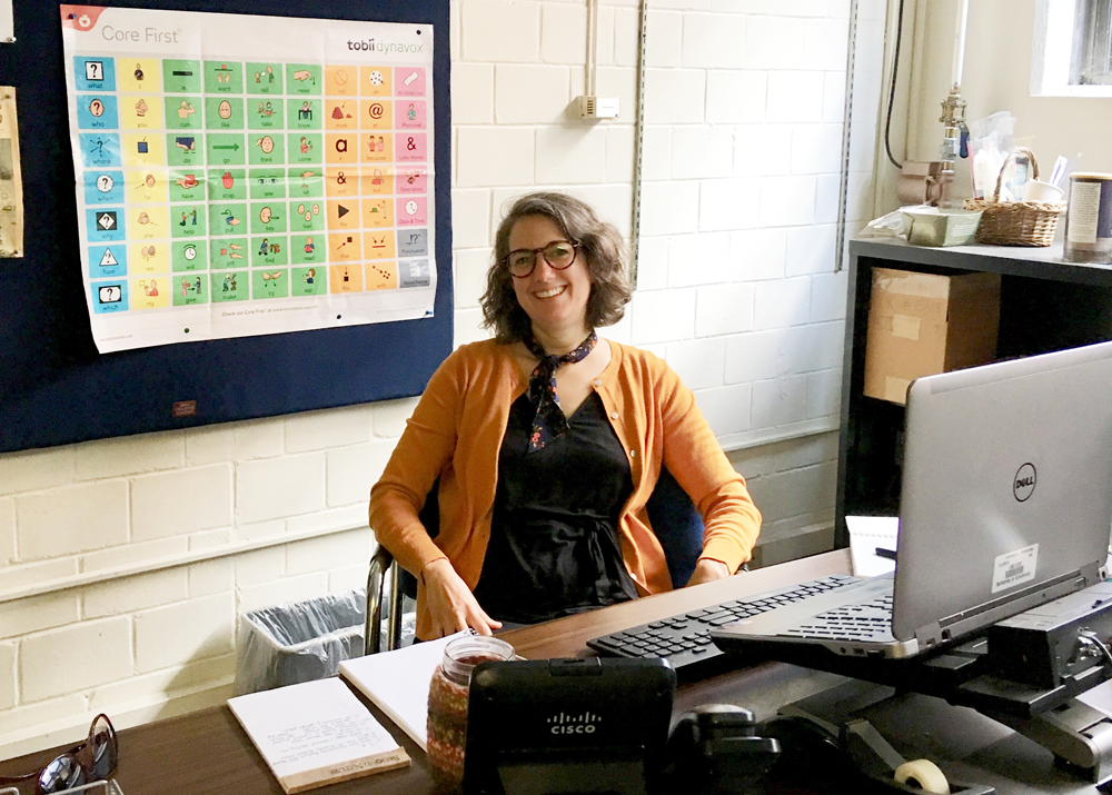 A woman with brown hair and black glasses wearing a black dress and copper sweater seated at a brown desk with white papers on it. A silver laptop is on her desk next to office supplies and a telephone. There is a multi-colored chart behind her.