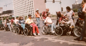 People using wheelchairs to move along the street in protest