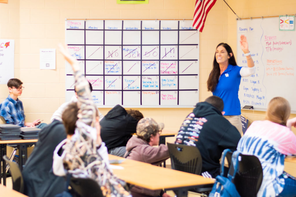 Woman with long brown hair wearing a blue shirt in front of a classroom of 7 students wearing a black sweatshirt, burgundy sweatshirt and hat, black sweatshirt with multi-colored lettering, tie dye blue and pink shirt, blue flannel shirt, navy sweatshirt. One student, wearing a white sweatshirt with black cartoons on it, has his hand raised.