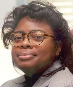 Debra Harley headshot. She is wearing a grey blazer. She has long, curly black hair and is wearing glasses.