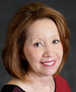Dr. Capilouto is smiling on front of a grey background. She has shoulder-length, red hair and is wearing red lipstick.