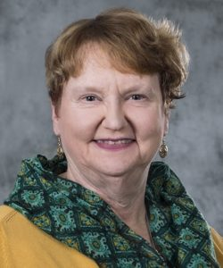 Jane Kleinert headshot. She is wearing a yellow sweater with a green, paisley scarf. She has short, red hair. She is also wearing gold earrings.