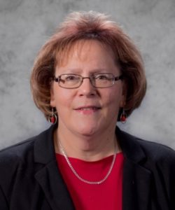 Judith Page headshot. She is wearing a red shirt and black blazer with a silver necklace and red bead earrings. She has short, auburn hair. She is wearing glasses.