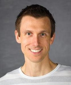 headshot of Ryan Hargrove. He has short, brown hair and is wearing a white and grey striped t-shirt.