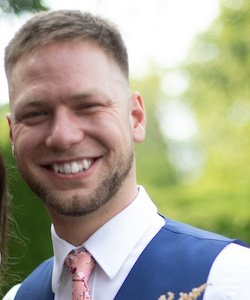 Jon Watkins staff photo. He is wearing a white collared shirt with a blue vest and a pink floral tie. He has shirt, brown hair and a beard. He is smiling.