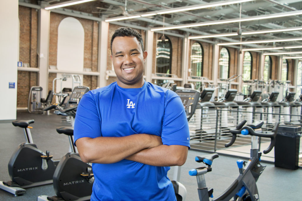 Morgan Turner wearing a UK blue t-shirt in a gym. He is smiling at the camera and has short, black hair.