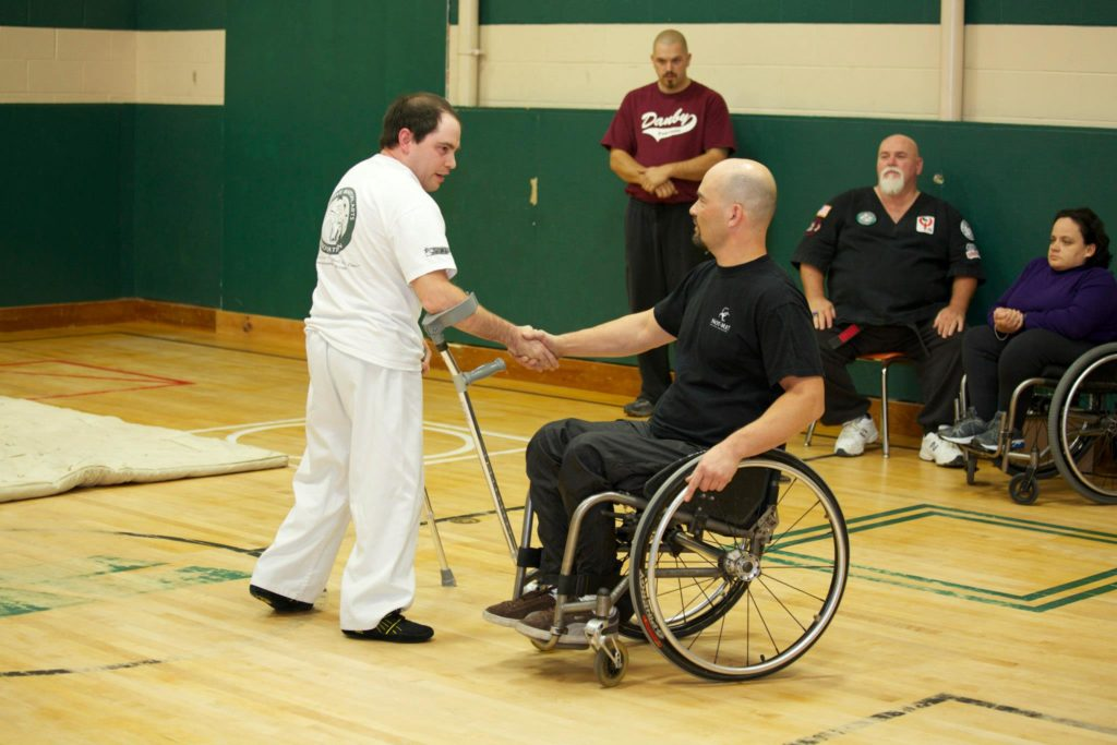 two male martial artists shaking hands; one man is wearing white and is standing and the other man is wearing black and uses a wheelchair for mobility. Three martial artists are shown in the background.