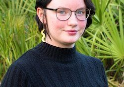 young woman wearing a black sweater, black glasses, and gold earrings standing in front of palm trees