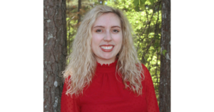 woman standing in front of trees is smiling has blonde hair and is wearing a red sweater