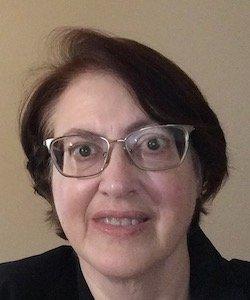 Deborah Hendricks staff photo. She is wearing a black shirt and glasses. She has short, red hair.
