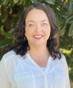 Kristy Ryan-Goodwin Staff photo. She is wearing a white blouse and has shoulder-length curly hair. She is standing in front of a tree and is smiling at the camera.