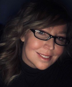 Lisa Hyde staff photo. She is wearing a black sweater with black rimmed glasses. She is smiling at the camera