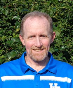 Christopher Rudolf staff photo. He is wearing a UK blue polo and has short hair and a beard. He is smiling at the camera and is standing in front of a bush.
